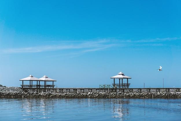 Três pavilhões estão localizados no rio rochoso e o céu azul é brilhante.