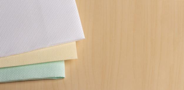 Três peças coloridas de tecido de ponto cruz de tela de bordado
