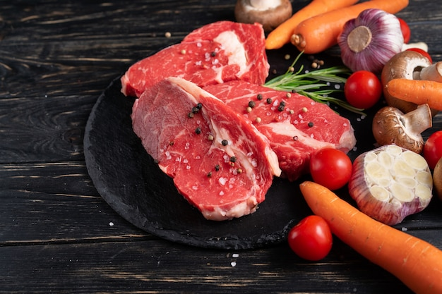 Três pedaços de carne crua suculenta com legumes em uma tábua de pedra em um fundo de mesa de madeira preto.