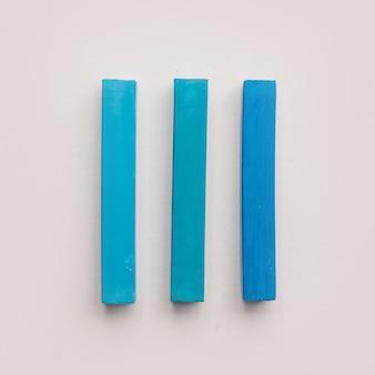 Três pedaços de giz de cera azul pastel