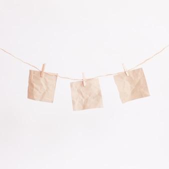 Três pedaços de papel adesivo quadrado bege em branco pendurado na corda do barbante com pequenos alfinetes no fundo branco isolado.