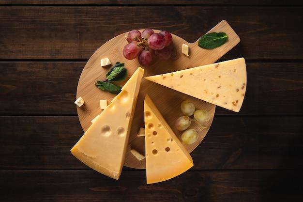 Três pedaços de queijo suíço amarelo com buracos e um galho de uvas vermelhas em uma tábua contra uma superfície de madeira, vista superior
