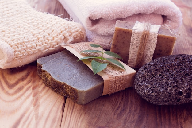 Três pedaços de sabão seco com uma toalha, pedra-pomes e bast