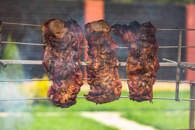 Três pedaços de shish kebab de porco são condimentados com especiarias e cozidos em um espeto acima do fogo perto da casa em clima quente