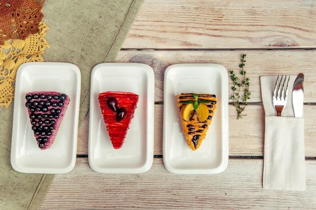 Três pedaços triangulares de bolo com ameixa damasco e groselha na mesa rústica de madeira