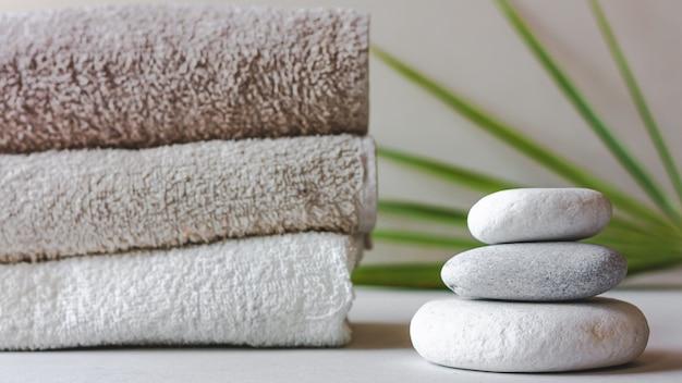 Três pedras redondas de spa cinza e toalhas de banho em fundo branco com folhas verdes.