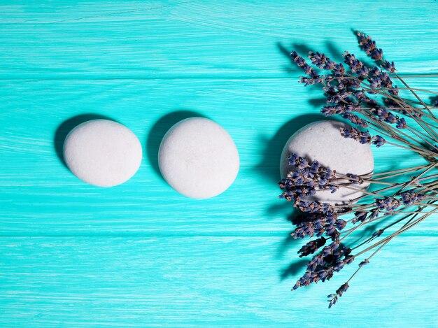 Três pedras zen brancas em uma linha em um fundo azul.