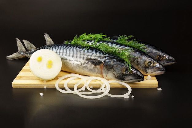 Três peixes cavala, decorados com endro, repousam sobre uma tábua ao lado de anéis de cebola e sal grosso em uma superfície preta.