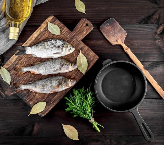 Três peixes do rio em uma placa de madeira marrom e uma frigideira de ferro fundido preto
