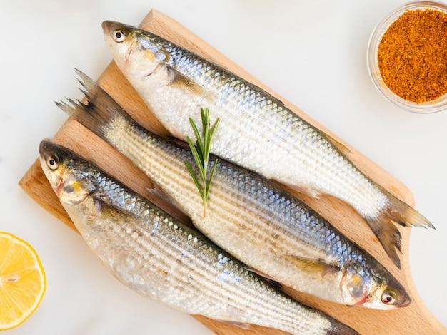 Três peixes frescos no fundo de madeira com condimentos