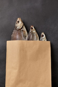 Três peixes salgados e secos em saco de papel kraft