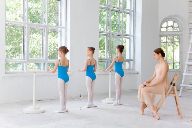 Três pequenas bailarinas dançando com o professor pessoal de balé no estúdio de dança