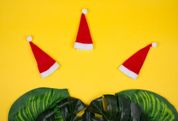 Três pequenos chapéus de papai noel e folhas tropicais