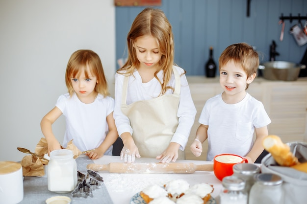 Três pequenos chefs desfrutando na cozinha fazendo grande confusão crianças fazendo biscoitos na cozinha