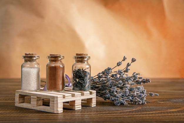 Três pequenos frascos cheios de açúcar, canela e chá em um carrinho de madeira com um ramo de lavanda em cima da mesa