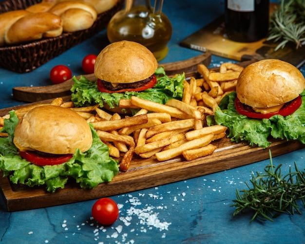 Três pequenos hambúrgueres de carne e batatas fritas, servidos na placa de madeira