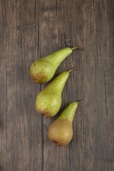 Três peras frescas maduras colocadas em superfície de madeira
