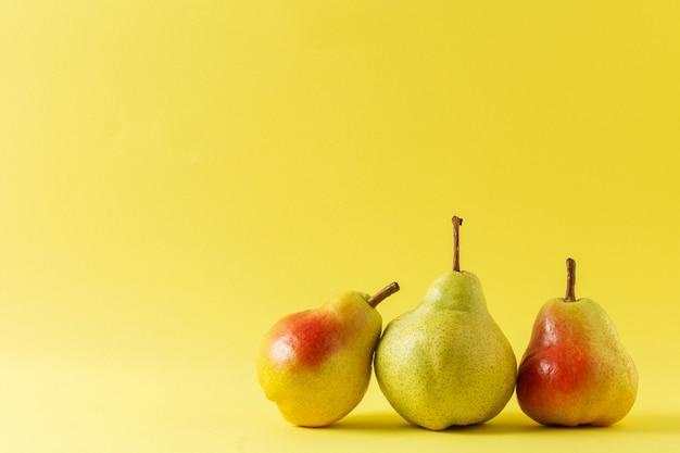 Três peras maduras em fundo amarelo. copie o espaço
