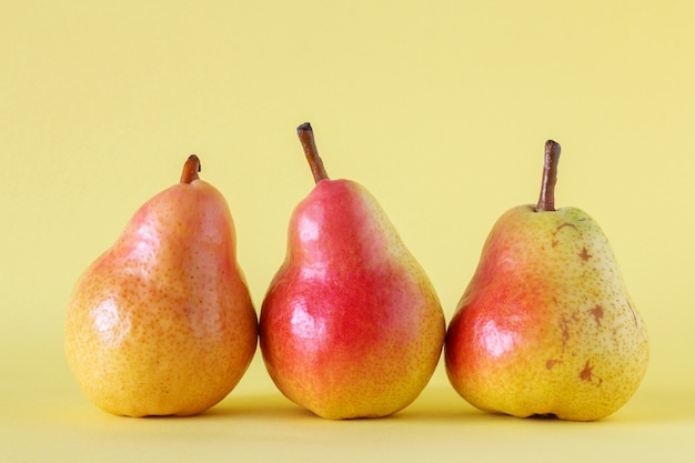 Três peras maduras em fundo amarelo.