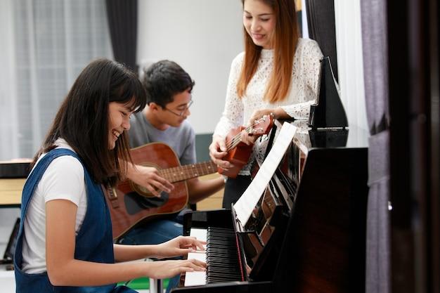 Três pessoas asiáticas família mãe filho e filha tocando música juntos