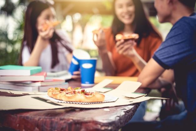 Três pessoas asiáticas gostam de comer pizza ao ar livre depois da aula de tutoria