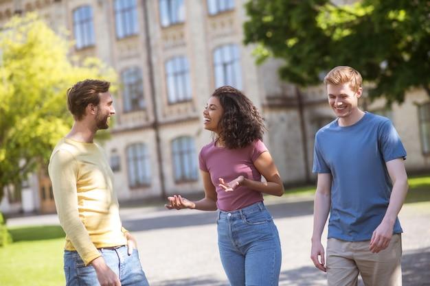 Três pessoas caminhando no parque e discutindo algo