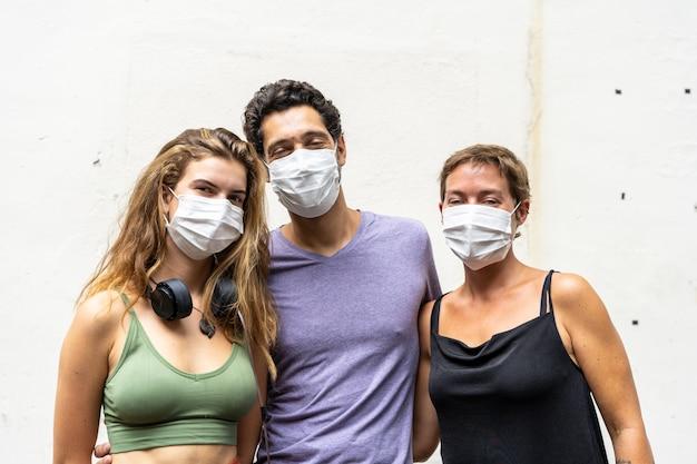 Três pessoas caucasianas com uma máscara no rosto