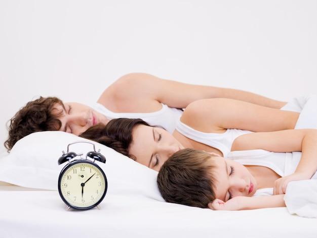 Três pessoas da jovem família dormindo com despertador perto de suas cabeças