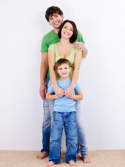Três pessoas da jovem família feliz e sorridente