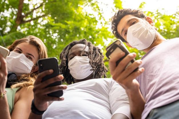 Três pessoas de diferentes etnias, juntamente com um telefone celular na mão usando máscaras de proteção
