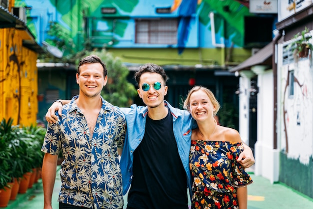 Três pessoas de diferentes etnias se abraçando pelas costas no meio de uma rua com fachadas coloridas decoradas com arte de rua