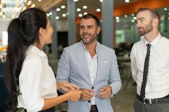 Três pessoas de negócios positivo conversando no lobby do escritório