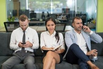 Três pessoas de negócios, sentado no sofá e tomando café