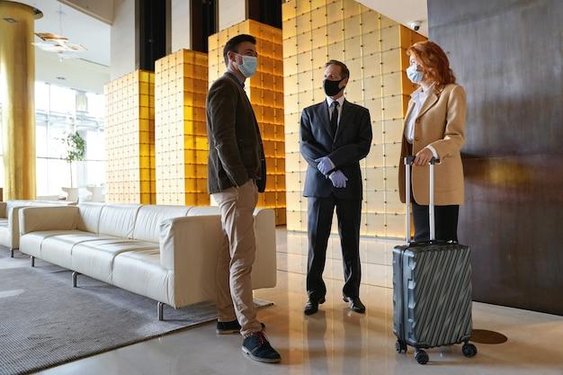 Três pessoas em pé no saguão de um hotel usando máscaras médicas de acordo com as precauções sanitárias