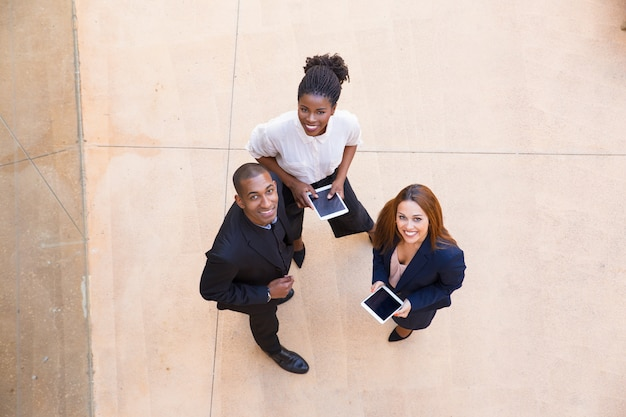 Três pessoas felizes com tablet posando