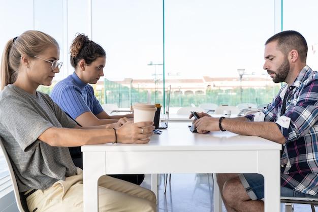Três pessoas se reuniram em uma mesa com laptops e café em uma reunião