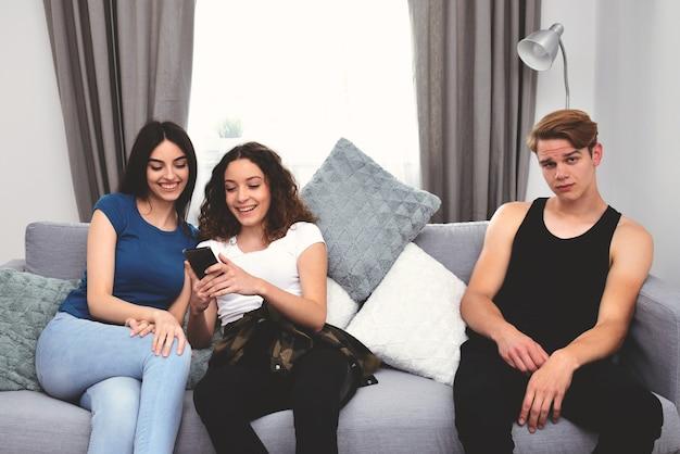 Três pessoas sentadas no sofá, duas olhando para um telefone, a terceira está entediada