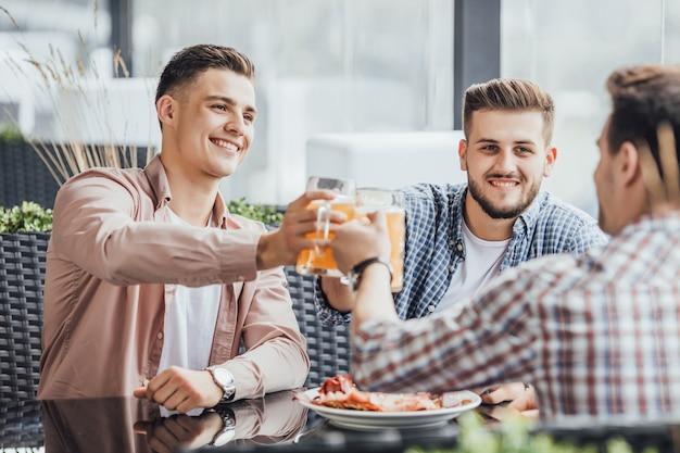 Três pessoas têm um bom dia, eles torcendo no café no terraço de verão com cervejas