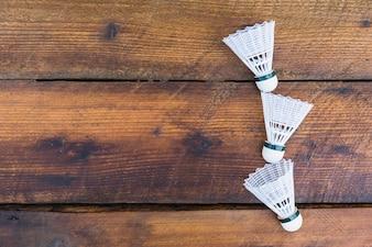 Três petecas no plano de fundo texturizado de madeira