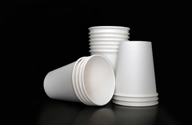 Três pilhas de copos de papel branco