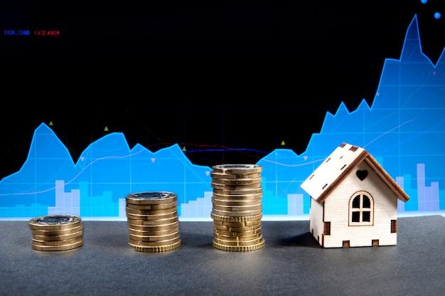 Três pilhas de moedas e uma casa de madeira
