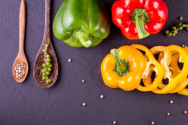 Três pimentas doces em um fundo de madeira, cozinhar salada de legumes