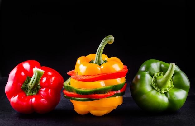 Três pimentões em um fundo de madeira, salada de legumes para cozinhar Foto Premium