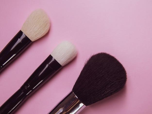 Três pincéis de maquiagem em um fundo rosa. pincéis profissionais para rímel e pó. maquiagem