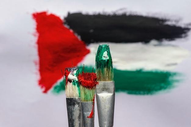 Três pincéis na frente da pintura desfocada da bandeira da palestina com fundo de papel branco, foco selecionado.