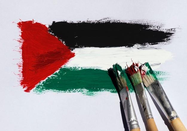 Três pincéis na pintura da bandeira da palestina em um fundo de papel branco, foco selecionado.