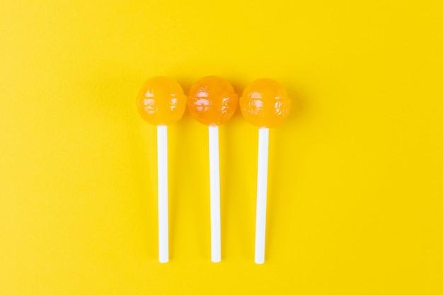 Três pirulitos amarelos sobre um fundo amarelo brilhante.