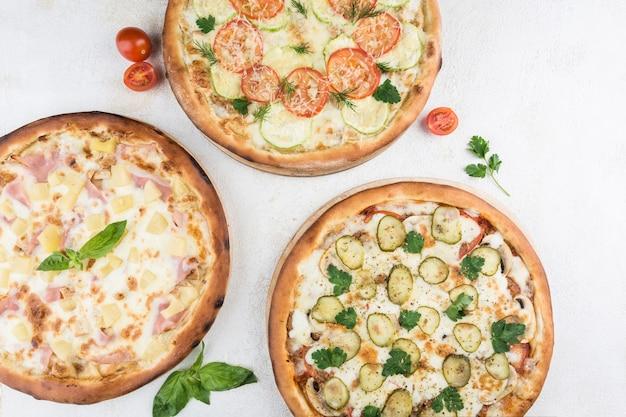 Três pizzas com recheios diferentes de frango, presunto, cogumelos, abacaxi, tomate, queijo mussarela e parmesão em um fundo claro. vista superior com um espaço de cópia para o texto. comida italiana.