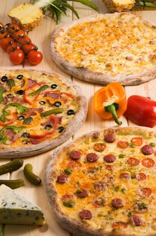 Três pizzas sortidas saborosas em um fundo de madeira publicidade conceito de pizza