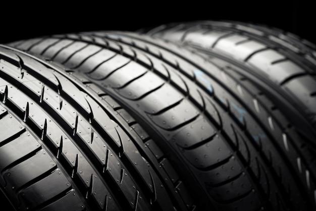 Três pneus de carro novos em um fundo preto escuro.